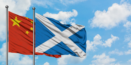 China and Scotland flag waving in the wind against white cloudy blue sky together. Diplomacy concept, international relations.