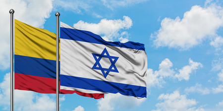 Colombia and Israel flag waving in the wind against white cloudy blue sky together. Diplomacy concept, international relations. Stock Photo