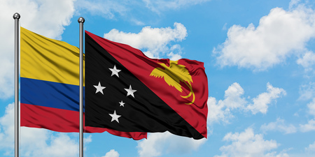 Colombia and Papua New Guinea flag waving in the wind against white cloudy blue sky together. Diplomacy concept, international relations. Stock Photo