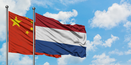 China and Netherlands flag waving in the wind against white cloudy blue sky together. Diplomacy concept, international relations.
