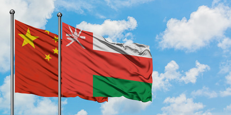 China and Oman flag waving in the wind against white cloudy blue sky together. Diplomacy concept, international relations.