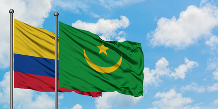 Colombia and Mauritania flag waving in the wind against white cloudy blue sky together. Diplomacy concept, international relations.