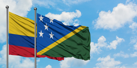 Colombia and Solomon Islands flag waving in the wind against white cloudy blue sky together. Diplomacy concept, international relations.