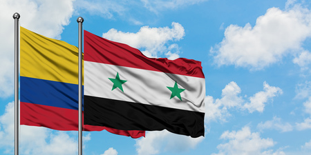 Colombia and Syria flag waving in the wind against white cloudy blue sky together. Diplomacy concept, international relations.