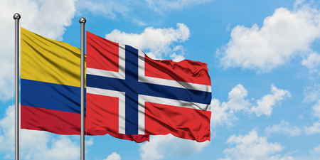 Colombia and Bouvet Islands flag waving in the wind against white cloudy blue sky together. Diplomacy concept, international relations. Stock Photo