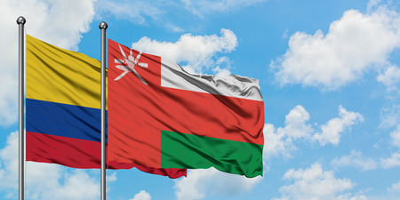 Colombia and Oman flag waving in the wind against white cloudy blue sky together. Diplomacy concept, international relations. Stock Photo