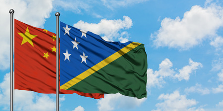 China and Solomon Islands flag waving in the wind against white cloudy blue sky together. Diplomacy concept, international relations. Stok Fotoğraf
