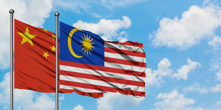 China and Malaysia flag waving in the wind against white cloudy blue sky together. Diplomacy concept, international relations.