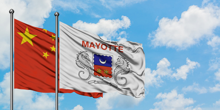 China and Mayotte flag waving in the wind against white cloudy blue sky together. Diplomacy concept, international relations.