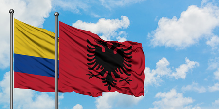 Colombia and Albania flag waving in the wind against white cloudy blue sky together. Diplomacy concept, international relations. Stock Photo