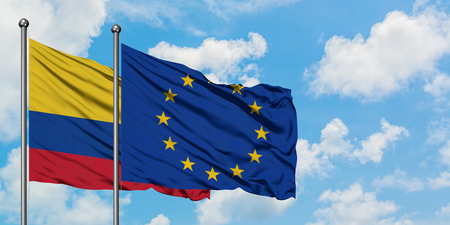 Colombia and European Union flag waving in the wind against white cloudy blue sky together. Diplomacy concept, international relations. Stock Photo