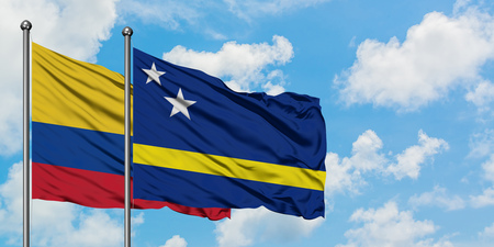 Colombia and Curacao flag waving in the wind against white cloudy blue sky together. Diplomacy concept, international relations.
