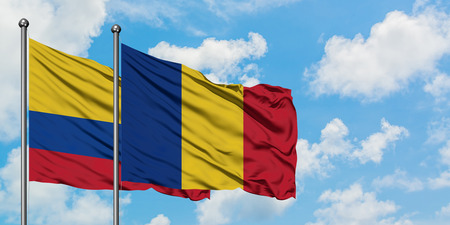 Colombia and Romania flag waving in the wind against white cloudy blue sky together. Diplomacy concept, international relations.