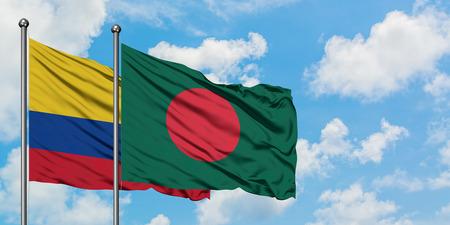 Bandera de Colombia y Bangladesh ondeando en el viento contra el cielo azul nublado blanco juntos. Concepto de diplomacia, relaciones internacionales. Foto de archivo