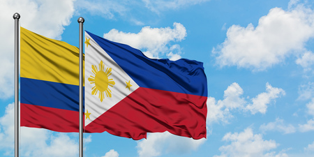 Colombia and Philippines flag waving in the wind against white cloudy blue sky together. Diplomacy concept, international relations.