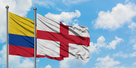 Colombia and England flag waving in the wind against white cloudy blue sky together. Diplomacy concept, international relations.
