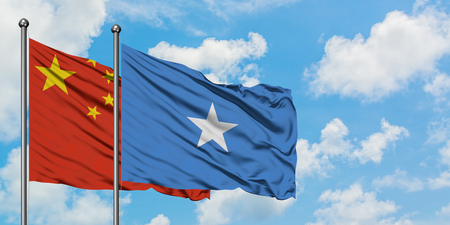 China and Somalia flag waving in the wind against white cloudy blue sky together. Diplomacy concept, international relations. Stock Photo