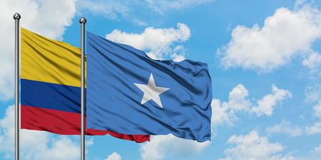 Colombia en Somalië vlag zwaaien in de wind tegen witte bewolkte blauwe hemel samen. Diplomatie concept, internationale betrekkingen.