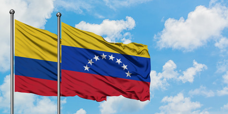 Colombia and Venezuela flag waving in the wind against white cloudy blue sky together. Diplomacy concept, international relations. 免版税图像