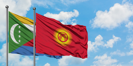 Comoros and Kyrgyzstan flag waving in the wind against white cloudy blue sky together. Diplomacy concept, international relations.