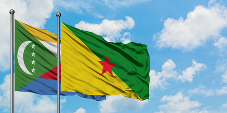 Comoros and French Guiana flag waving in the wind against white cloudy blue sky together. Diplomacy concept, international relations.
