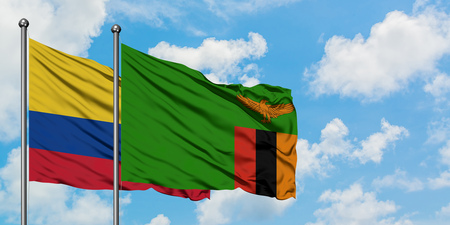 Colombia and Zambia flag waving in the wind against white cloudy blue sky together. Diplomacy concept, international relations. Stock Photo