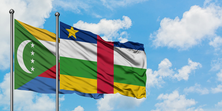 Comoros and Central African Republic flag waving in the wind against white cloudy blue sky together. Diplomacy concept, international relations.