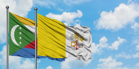 Comoros and Vatican City flag waving in the wind against white cloudy blue sky together. Diplomacy concept, international relations.
