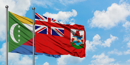 Comoros and Bermuda flag waving in the wind against white cloudy blue sky together. Diplomacy concept, international relations.