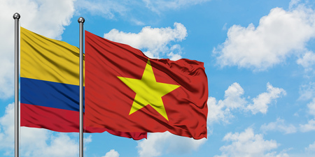 Colombia and Vietnam flag waving in the wind against white cloudy blue sky together. Diplomacy concept, international relations. Stock Photo