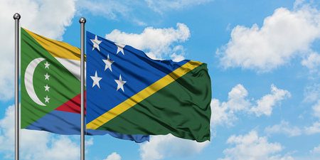 Comoros and Solomon Islands flag waving in the wind against white cloudy blue sky together. Diplomacy concept, international relations.