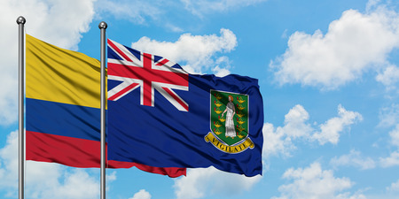 Colombia and British Virgin Islands flag waving in the wind against white cloudy blue sky together. Diplomacy concept, international relations.
