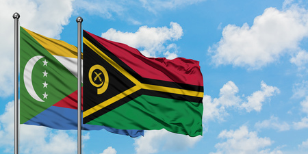 Comoros and Vanuatu flag waving in the wind against white cloudy blue sky together. Diplomacy concept, international relations.