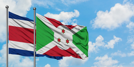 Costa Rica and Burundi flag waving in the wind against white cloudy blue sky together. Diplomacy concept, international relations.