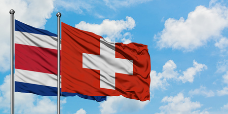 Costa Rica and Switzerland flag waving in the wind against white cloudy blue sky together. Diplomacy concept, international relations.