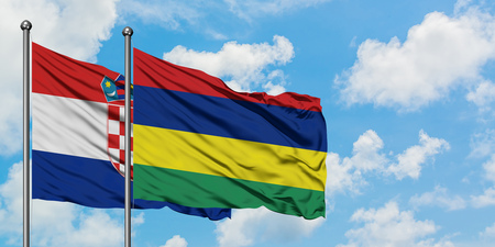 Croatia and Mauritius flag waving in the wind against white cloudy blue sky together. Diplomacy concept, international relations.