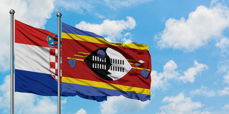 Croatia and Swaziland flag waving in the wind against white cloudy blue sky together. Diplomacy concept, international relations. 免版税图像