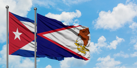 Cuba and American Samoa flag waving in the wind against white cloudy blue sky together. Diplomacy concept, international relations.