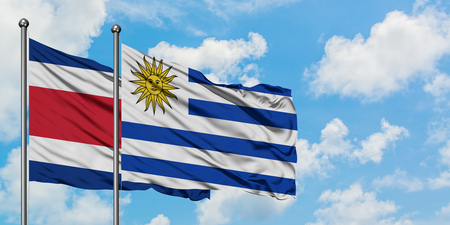 Costa Rica and Uruguay flag waving in the wind against white cloudy blue sky together. Diplomacy concept, international relations. Banco de Imagens