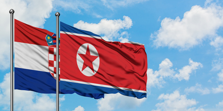 Croatia and North Korea flag waving in the wind against white cloudy blue sky together. Diplomacy concept, international relations.