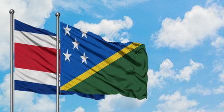 Costa Rica and Solomon Islands flag waving in the wind against white cloudy blue sky together. Diplomacy concept, international relations. Stok Fotoğraf