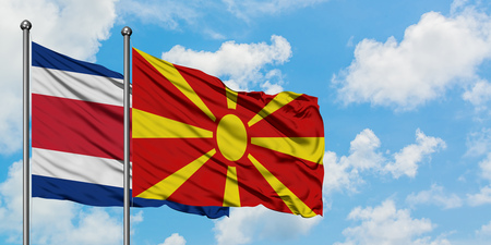 Costa Rica and Macedonia flag waving in the wind against white cloudy blue sky together. Diplomacy concept, international relations.