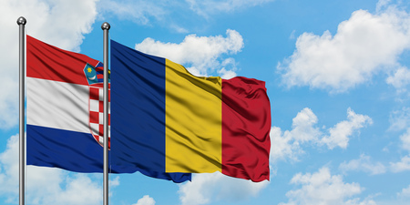 Croatia and Romania flag waving in the wind against white cloudy blue sky together. Diplomacy concept, international relations. Фото со стока