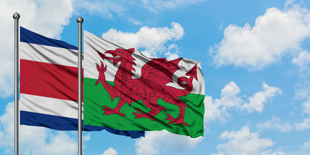 Costa Rica and Wales flag waving in the wind against white cloudy blue sky together. Diplomacy concept, international relations.