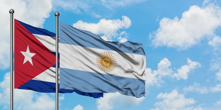 Cuba and Argentina flag waving in the wind against white cloudy blue sky together. Diplomacy concept, international relations.
