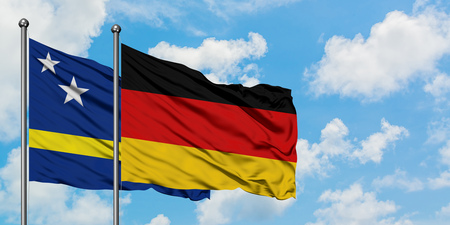 Curacao and Germany flag waving in the wind against white cloudy blue sky together. Diplomacy concept, international relations. Stock Photo