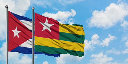 Cuba and Togo flag waving in the wind against white cloudy blue sky together. Diplomacy concept, international relations. Stock Photo