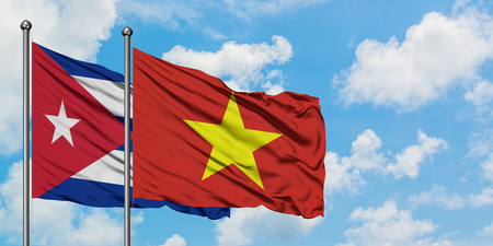 Cuba and Vietnam flag waving in the wind against white cloudy blue sky together. Diplomacy concept, international relations. Stock Photo