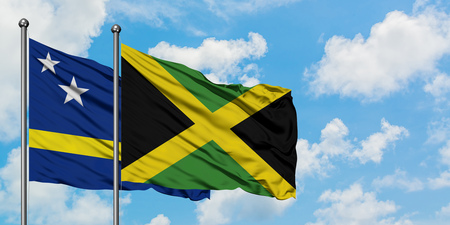 Curacao and Jamaica flag waving in the wind against white cloudy blue sky together. Diplomacy concept, international relations.