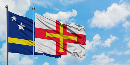 Curacao and Guernsey flag waving in the wind against white cloudy blue sky together. Diplomacy concept, international relations.